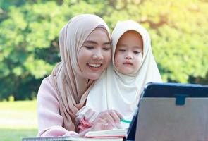 Muslim mother and daughter enjoying their holiday in the park photo
