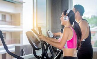 Beautiful Asian woman is exercising in a gym with a personal trainer photo