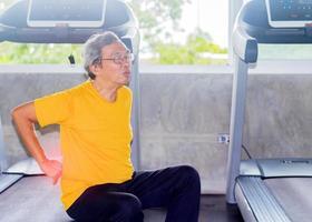 Un hombre asiático con gafas sentado en el suelo debido al dolor en la espalda por hacer ejercicio en el gimnasio foto