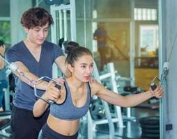 Asian woman is exercising in a gym with a personal trainer photo