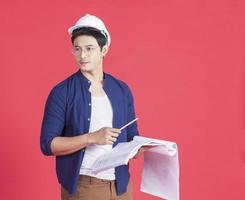 Retrato de joven arquitecto con un casco blanco sosteniendo un plan de construcción sobre un fondo rojo. foto