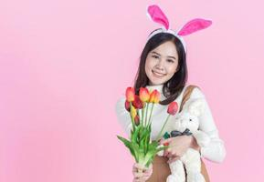 Asian young woman wearing bunny ears holding a tulip on a pink background photo