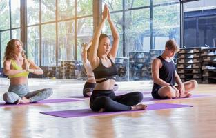 Group practicing yoga in the gym, concept of healthy exercise and meditation photo
