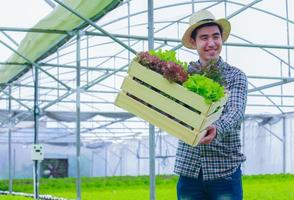 Asian farmer holds a basket of organic vegetables and smiles happily photo