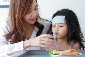 Childhood daughter caring for a mother who is sick at home photo