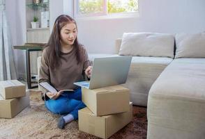 Hermosa mujer asiática sentada en casa y trabajando en línea, envío de negocios en línea foto