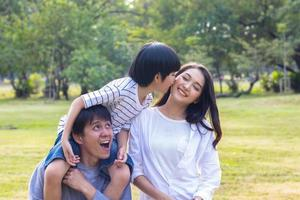 Asian family enjoys sitting in the park on the autumn holiday photo