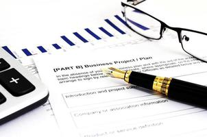 Business project plan withfountain pen and calculator and eyeglasses photo