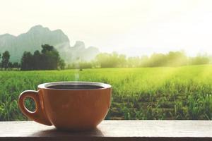 Café caliente negro caliente con humo sobre una mesa de madera con un paisaje de la naturaleza con la montaña en el tiempo de la mañana foto