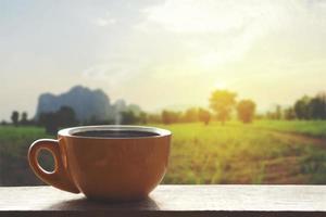 Café caliente negro caliente con humo sobre una mesa de madera con un paisaje de naturaleza con montaña foto