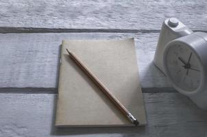 A book and pencil with alarm clock on an old wood table photo