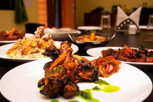 The concept of Indian cuisine chicken legs with spices and shoes photo