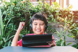 Asian cute boy playing games on the tablet photo