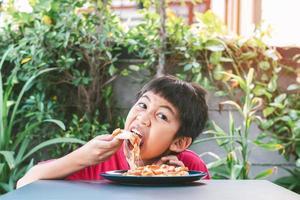 chico lindo asiático felizmente sentado comiendo pizza foto