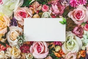 Beautiful colorful flowers wall background with white greeting card with copy space Spring wedding anniversary or florist greeting card photo