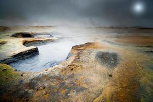 Piscina de barro caliente hirviendo en hverir islandia espectacular paisaje con luna llena foto