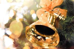 campanas de oro con un lazo rojo en un árbol de navidad, desenfoque de fondo bokeh brillante foto