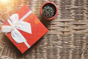Red gift box with white ribbon on woven bamboo wood background, cozy and warm welcome home concept photo