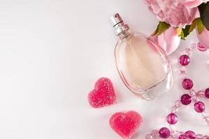 Bottle of perfume flowers and hearts on a light background photo