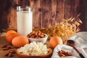 Cottage cheese eggs nuts and milk on a wooden background photo