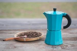 blue geyser coffee maker and roasted coffee beans on the background of an old wooden board photo