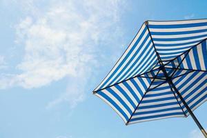 blue striped beach umbrella with sky background photo