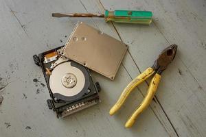 Disco duro roto y destruido y herramientas sobre mesa de madera foto