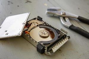 Disco duro roto y destruido en la mesa de madera foto