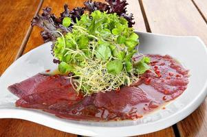 Carpaccio de pescado con ensalada de aceitunas ana servido en un plato blanco foto
