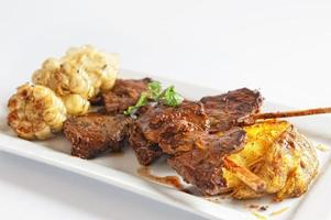 Grilled skewered beef heart meat with boiled potato and white corn photo