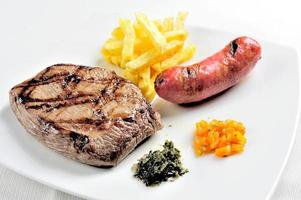 Grilled meat Meat chorizo and French fries with chimichurri sauce photo