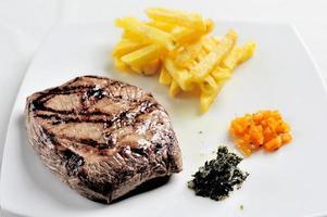 carne a la brasa y patatas fritas acompañadas de salsa chimichurri foto