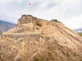 Aerial view to Gori castle walls with Georgian flags on top photo