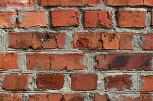 Old wall background with stained aged red bricks photo