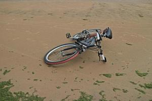Mountain bike lies on the sand on an empty beach photo