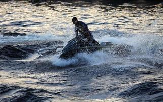 Jet ski at high speed lifts a large wave photo