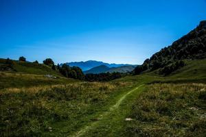 Camino entre los pastos en el monte altissimo cerca del lago de Garda, Trento, Italia foto