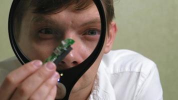 um técnico examina um microchip através de uma grande lupa iluminada video