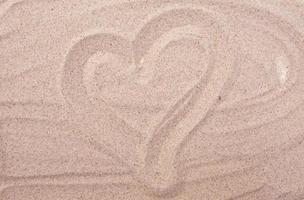 Heart drawing on sea sand photo