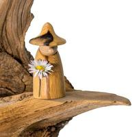 Turned wood gnome with a daisy in hand stands on an old tree stump photo