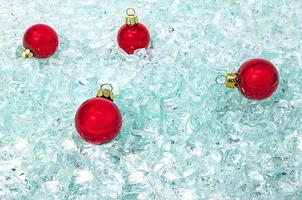 bolas de vidrio rojo con perchas de oro yacen sobre brillantes fragmentos de vidrio foto