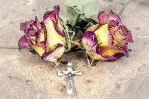 Christian cross on rosary and a dry yellow red roses lie on a sandstone photo