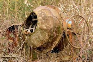 Old rusted cement mixer stands overgrown in a leafless thorn hedge photo