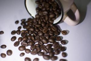 Roasted beans  and cup on white background photo