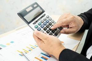 Contador asiático trabajando y analizando informes financieros, contabilidad de proyectos con gráfico y calculadora en la oficina moderna foto