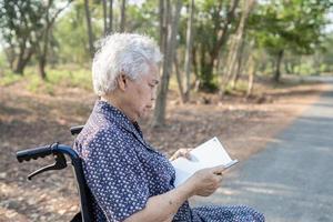 Paciente asiático mayor o anciano mujer leyendo un libro mientras está sentado en la cama en la sala del hospital de enfermería saludable concepto médico fuerte foto