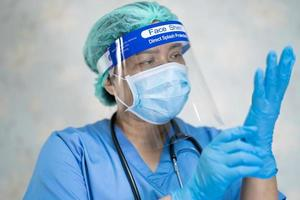 Asian doctor wearing face shield and PPE suit new normal to check patient protect safety infection Covid 19 Coronavirus outbreak at quarantine nursing hospital ward photo
