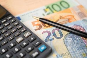 Dinero de los billetes en euros con calculadora en papel cuadriculado foto