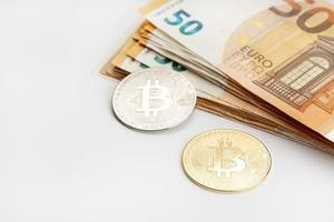 Bitcoin coins and Euro banknotes Cryptocurrency versus fiat money concept photo