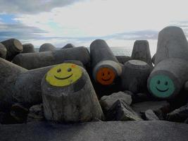 City, Country, MM DD, YYYY - Concrete blocks with colored faces on the beach shore photo